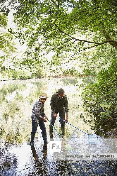 Vater und Sohn fischen mit Netzen im Teich