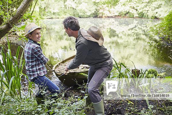 Vater und Sohn ziehen Boot an Land im Teich