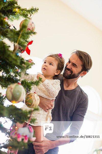 Vater und Tochter schmücken den Weihnachtsbaum