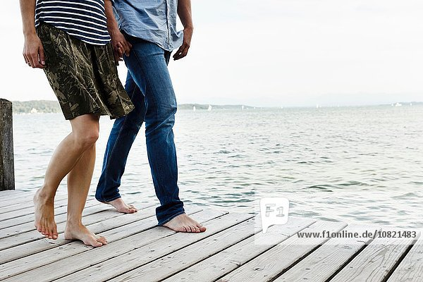 Ausschnitt eines romantischen Paares beim Spaziergang am Holzsteg  Starnberger See  Bayern  Deutschland