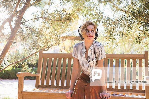 Mittlere erwachsene Frau sitzt auf der Bank  trägt Kopfhörer und schaut weg.