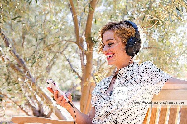 Mittlere erwachsene Frau auf der Bank sitzend  Kopfhörer tragend  Smartphone anschauend  lächelnd