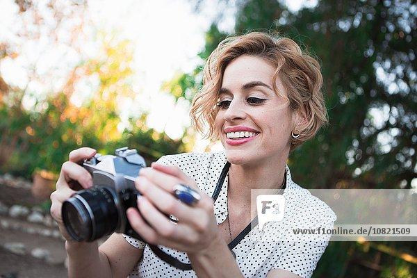 Mittlere erwachsene Frau mit Blick auf die Rückseite der Kamera  im Freien  lächelnd