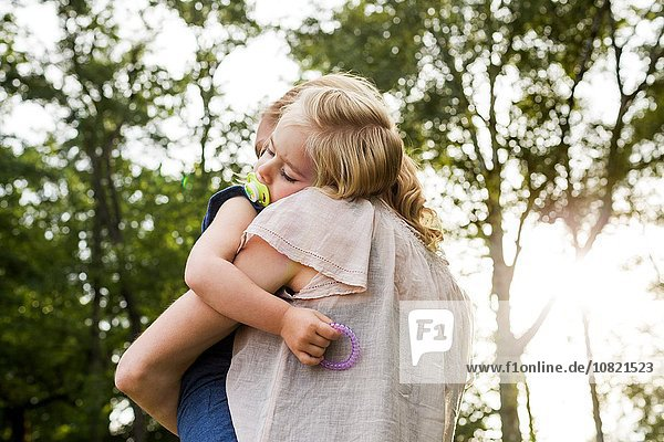Mid adult woman carrying sleeping daughter in park