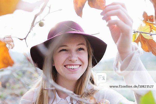 Junge Frau hält Blatt  lächelnd  draußen