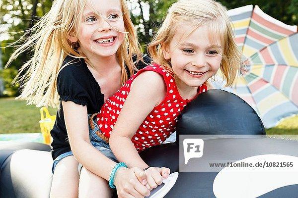 Zwei junge Schwestern sitzen auf einem aufblasbaren Wal im Park.