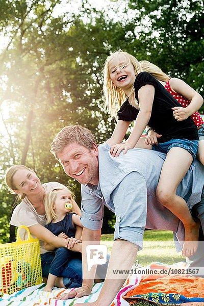 Vater schenkt Töchtern Huckepack beim Familienpicknick im Park