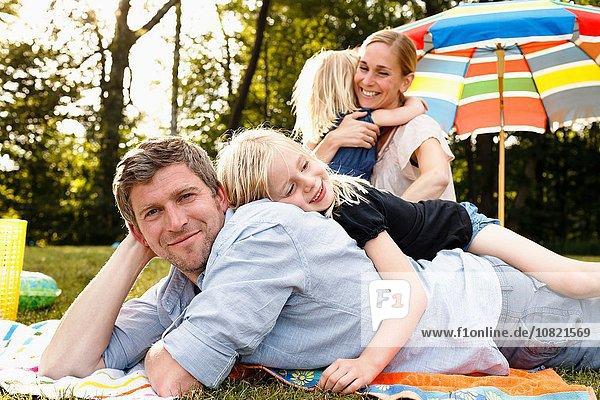 Junge Tochter auf Vater liegend beim Familienpicknick im Park