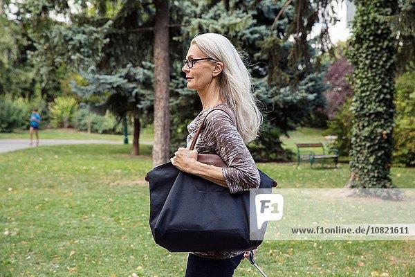 Mature woman walking through park carrying shoulder bag