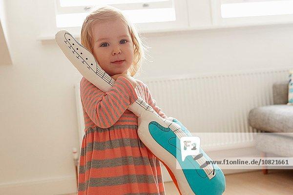 Porträt einer Kleinkindespielerin mit Spielzeuggitarre im Wohnzimmer