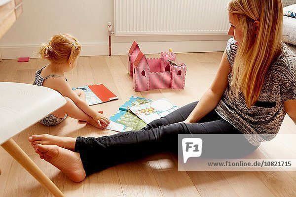 Woman and toddler daughter playing on living floor