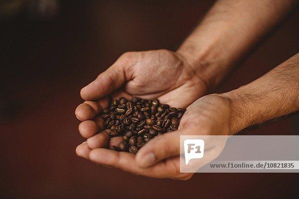Mann mit Kaffeebohnen  Nahaufnahme