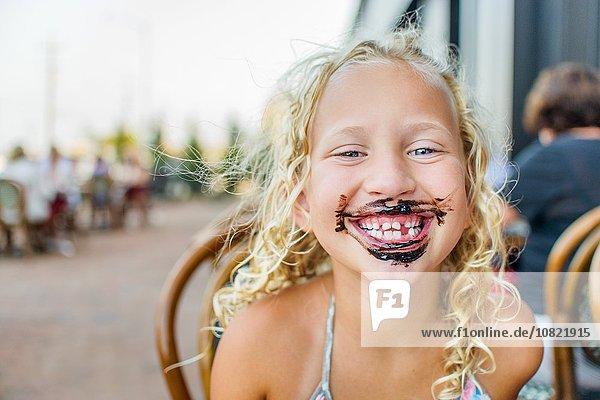 Porträt eines blondhaarigen Mädchens auf dem Bürgersteig Cafe mit Sauce bedeckt Mund Porträt eines blondhaarigen Mädchens auf dem Bürgersteig Cafe mit Sauce bedeckt Mund