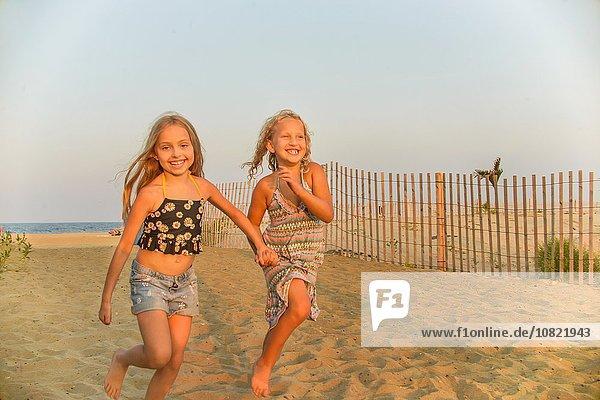 Porträt von blondhaarigen Schwestern  die Hand in Hand am Strand laufen. Porträt von blondhaarigen Schwestern, die Hand in Hand am Strand laufen.