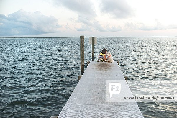 Rear view of girl sitting on sea pier petting dog