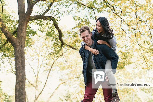 Mid adult man giving girlfriend a piggyback in park