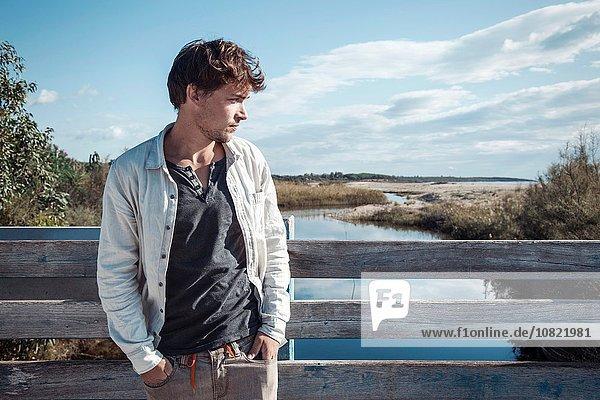 Junger Mann an Holzzaun auf Brücke über den Fluss gelehnt  Hände in Taschen  Costa Smeralda  Sardinien  Italien