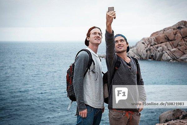 Junge Männer vor dem Meer mit dem Smartphone  um Selfie lächelnd zu nehmen  Costa Smeralda  Sardinien  Italien