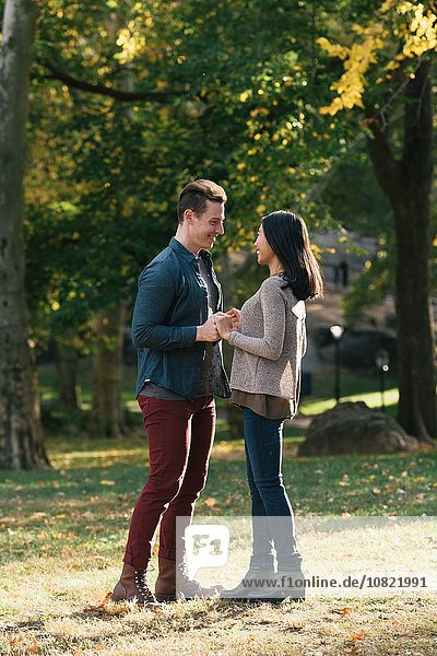 Romantic mid adult couple in park holding hands