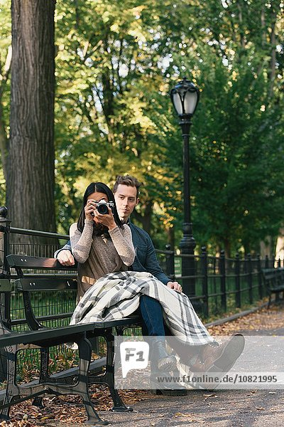 Mid adult woman sitting on park bench with boyfriend taking photographs on SLR camera