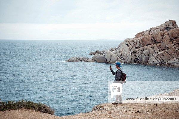 Junger Mann steht auf einer Klippe und fotografiert mit dem Smartphone den Ozean  Costa Smeralda  Sardinien  Italien