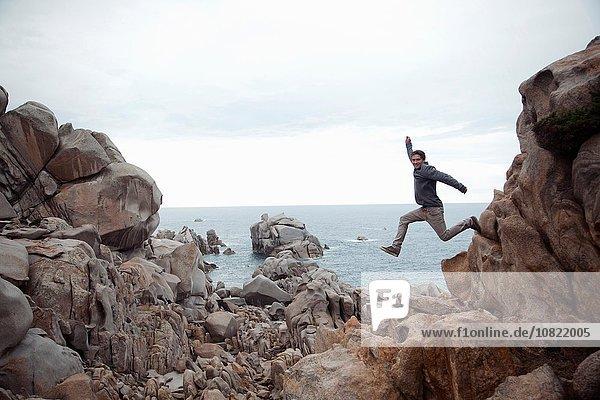 Seitenansicht eines jungen Mannes in der Luft  der von Felsen springt  lächelnd  Costa Smeralda  Sardinien  Italien