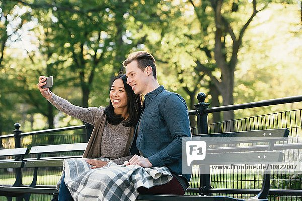 Mid adult couple sitting on park bench taking smartphone selfie