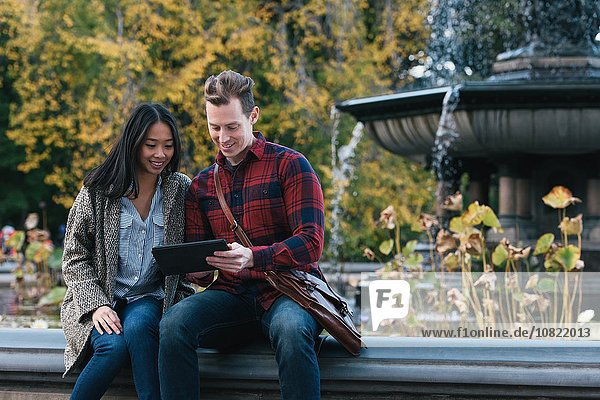 Mid adult couple reading digital tablet at Bethesda fountain in Central Park  New York  USA