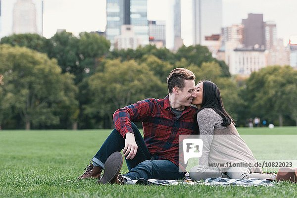 Romantic mid adult couple on picnic blanket in Central Park  New York  USA