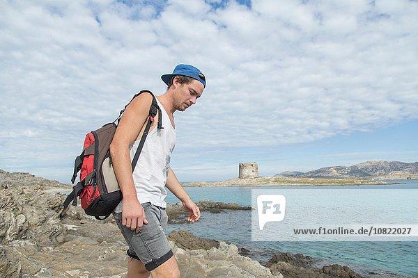 Junger Mann auf Felsen am Meer mit Rucksack mit Blick nach unten  Stintino  Sardinien  Italien