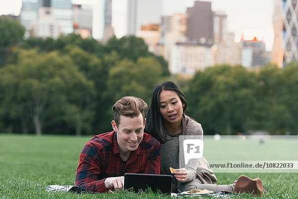 Mid adult couple on picnic blanket reading digital tablet in Central Park  New York  USA