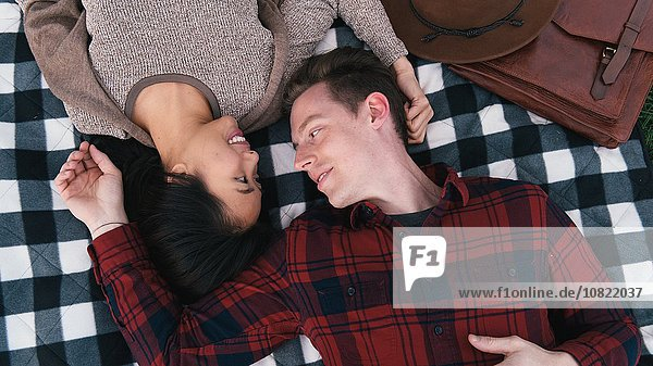 Overhead view of romantic mid adult couple lying on checker blanket