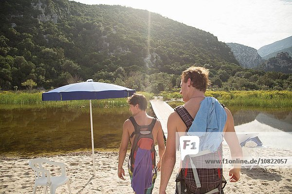 Rear view of young men carrying backpacks on beach  Cala Luna  Sardinia  Italy