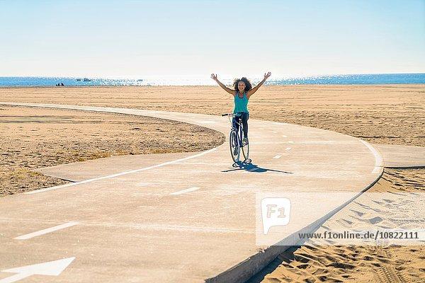 Mittlere erwachsene Frau  die am Strand entlang des Weges radelt  Arme in der Luft