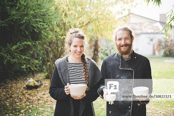 Paar im Garten mit Tontöpfen und lächelndem Blick auf die Kamera