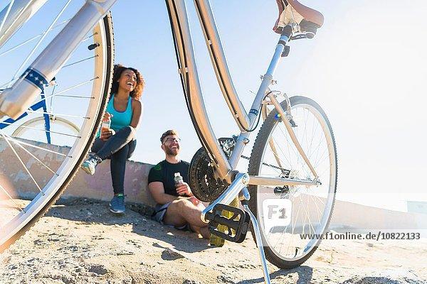 Pärchen entspannen nach der Radtour  Fahrräder daneben