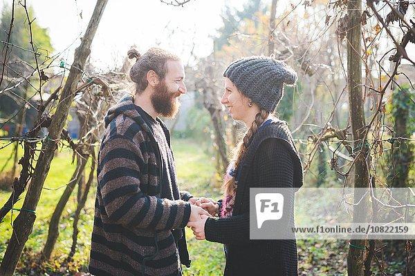 Seitenansicht des Paares zwischen den Bäumen von Angesicht zu Angesicht,  Händchen haltend,  lächelnd