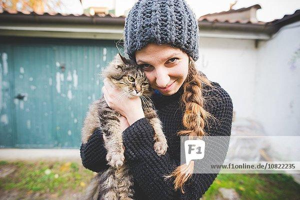 Junge Frau mit Strickmütze kuschelnde Katze  Blick auf die Kamera lächelnd Junge Frau mit Strickmütze kuschelnde Katze, Blick auf die Kamera lächelnd