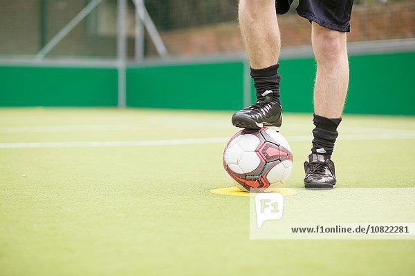 Junger Mann auf Stadtfußballplatz  Fuß auf Fußball  niedriger Abschnitt