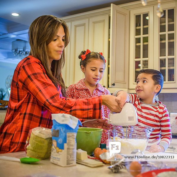 Mutter und Kinder in der Küche mit dem Schneebesen