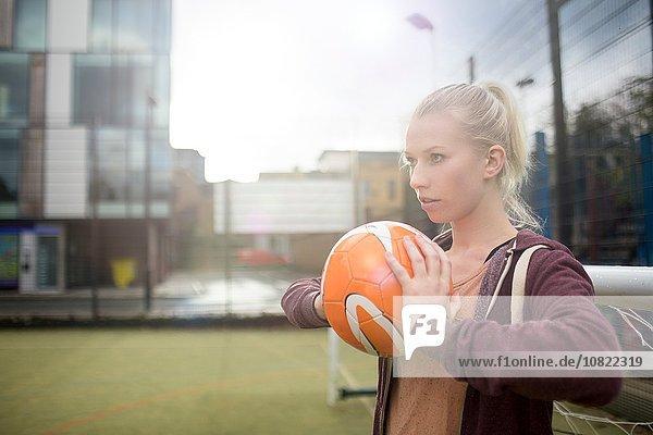 Junge Frau im Begriff  Fußball zu werfen