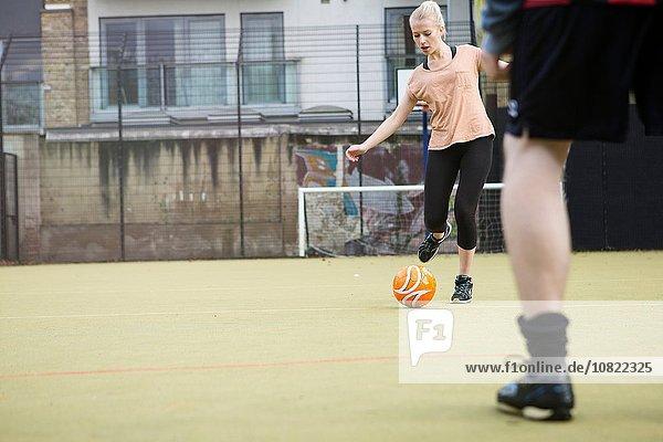 Junge Frau spielt Fußball auf dem Stadtfußballplatz