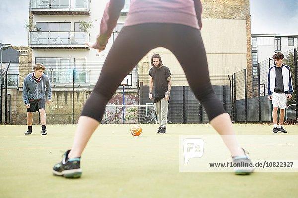Gruppe von Erwachsenen  die auf dem Stadtfußballplatz Fußball spielen
