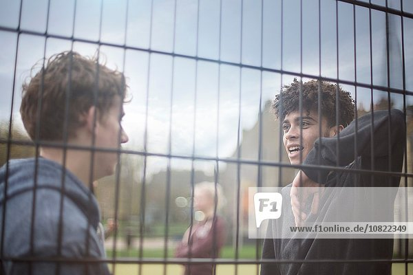 Zwei junge Männer  die sich gegen den Zaun lehnen und reden.