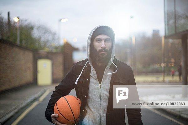 Porträt eines erwachsenen Mannes in der Straße  der Basketball hält.