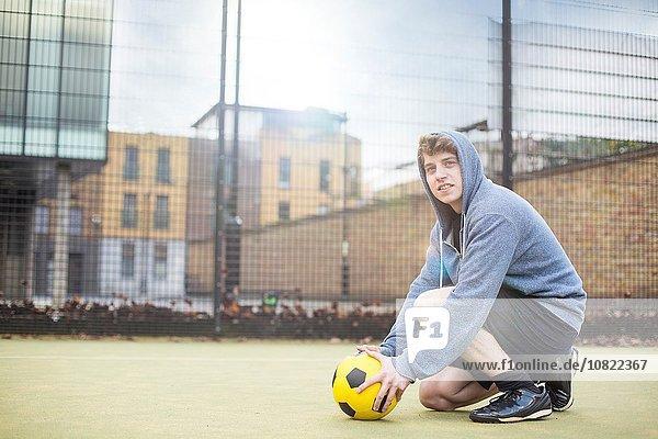 Junger Mann setzt Fußball auf den Boden  auf dem städtischen Fußballplatz