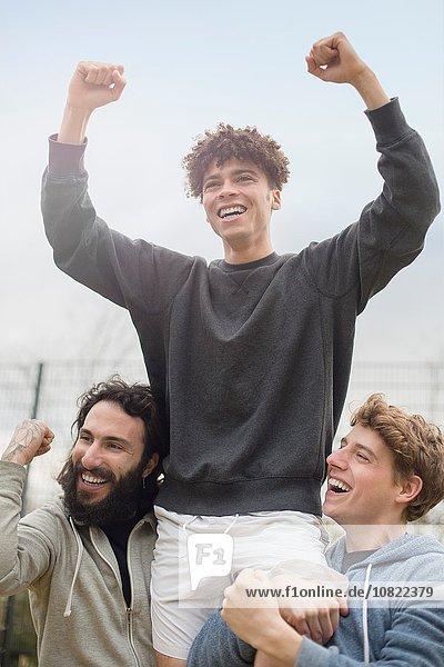 Junger Mann  der von zwei Freunden in die Luft gehoben wird  feiert