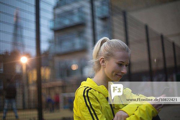 Junge Frau mit Smartphone  lächelnd