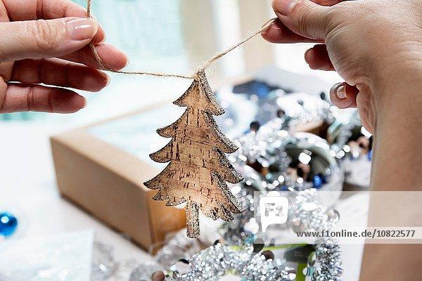 Personenhände beim Vorbereiten von Weihnachtsdekoration in Form eines Holzbaums