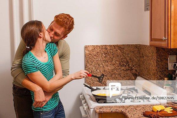 Junger Mann in der Küche Arme um junge Frau Kochen auf dem Herd  Küssen